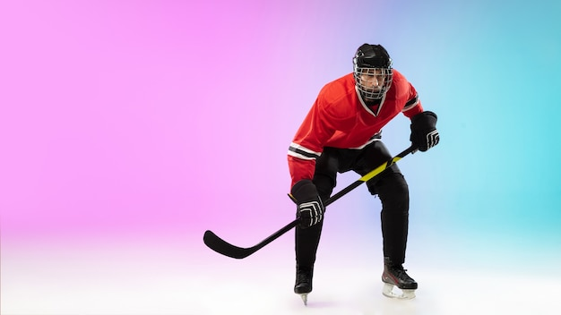 Male hockey player with the stick on ice court and neon colored gradient wall sportsman wearin...