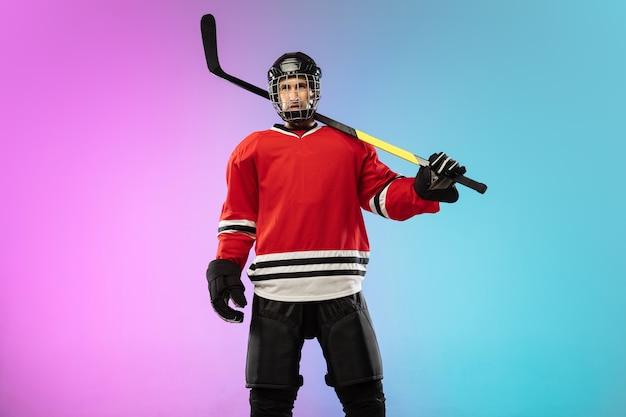 Giocatore di hockey maschio con il bastone sul campo da ghiaccio e lo spazio sfumato al neon