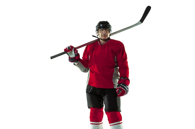 Male hockey player with the stick on ice court and white background.
