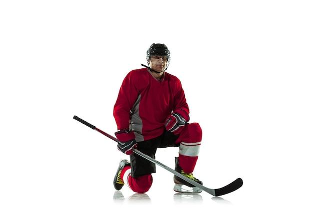 Giocatore di hockey maschio con il bastone sul campo da ghiaccio e sfondo bianco.