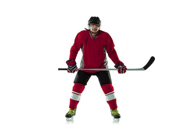 Giocatore di hockey maschio con il bastone sul campo da ghiaccio e muro bianco
