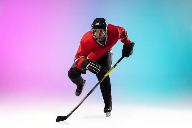 Male hockey player with the stick on ice court
