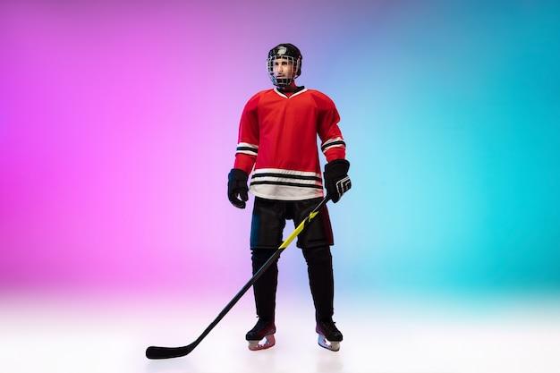Giocatore di hockey maschio con il bastone in posa sul campo da ghiaccio e parete sfumata colorata al neon