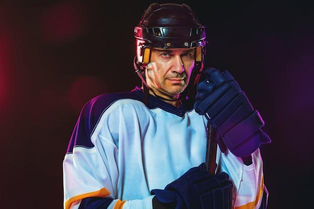 Хоккеист-мужчина с клюшкой на ледовой площадке и стене темного неонового цвета