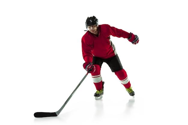 Мужской хоккеист с клюшкой на ледовой площадке и белом фоне.
