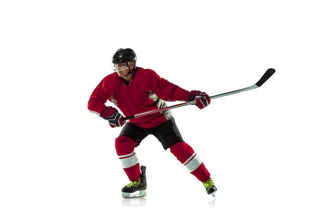 アイスコートと白い壁にスティックを持つ男性のホッケー選手