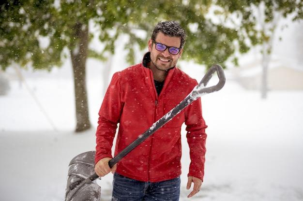 Мужчина держит снежную лопату и одет в красную куртку во время улыбки
