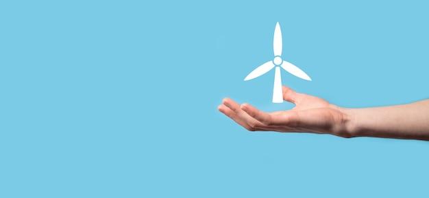 Мужчина держит значок ветряной мельницы, которая производит энергию окружающей среды на синей поверхности.