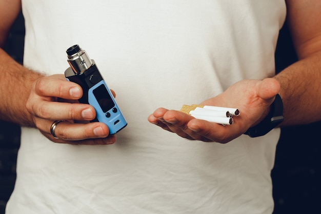 Male holding cigarettes and vape inhaler close up
