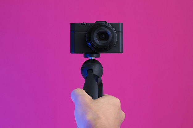 Мужчина держит компактную камеру в руке, делая видео блог. закройте
