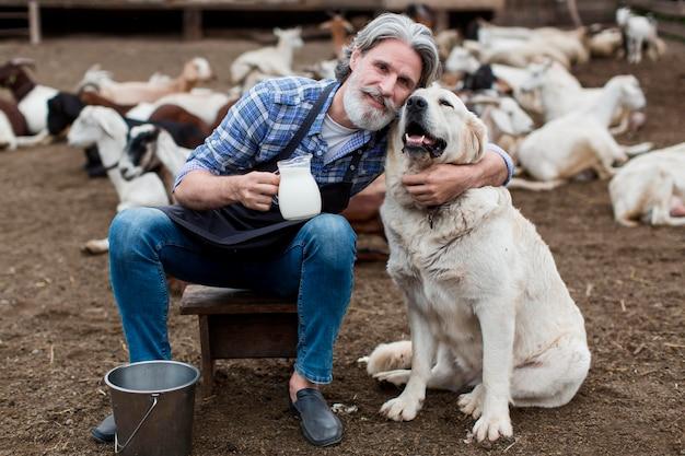 Мужчина держит чашку козьего молока, играя с собакой