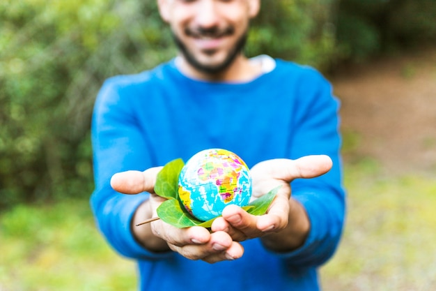 Male holding globe with green leaf and smiling