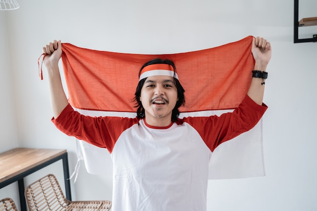インドネシアの旗を保持している男性。愛国的なナショナリズムの概念