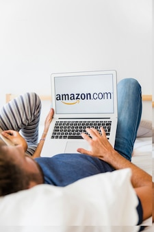 Male holding laptop on bed