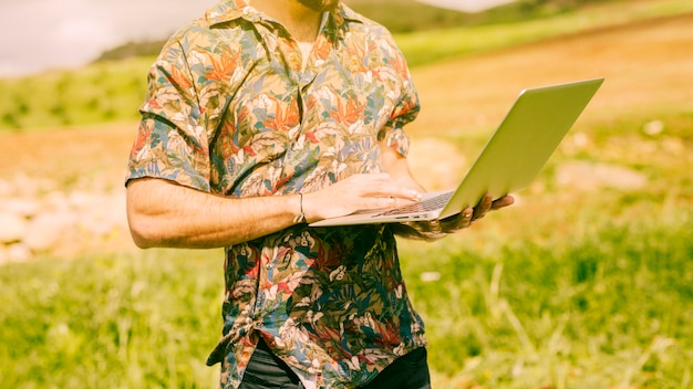 Male holding laptop in field