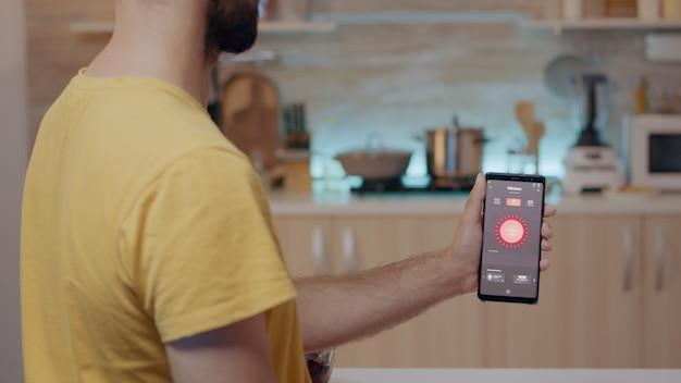 キッチンに座っている照明制御アプリでモバイルを保持している男性