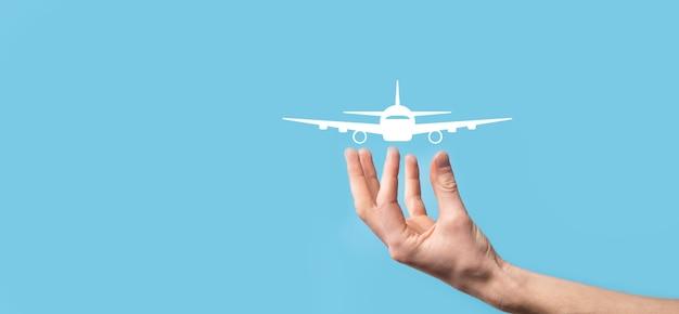 Мужчина держит значок самолета самолет на синей поверхности.