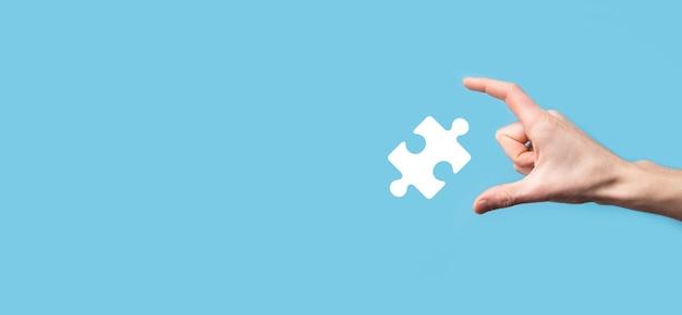青い表面にパズルアイコンを保持している男性。