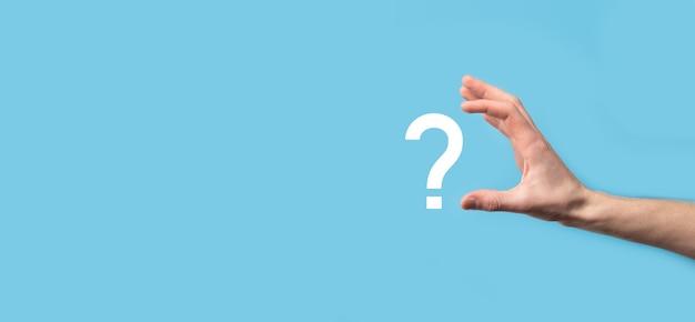 Мужчина держит значок вопросительного знака на синей поверхности. баннер с копией пространства. место для текста.