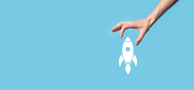 Мужчина держит значок ракеты, который взлетает, запускает на синей поверхности.