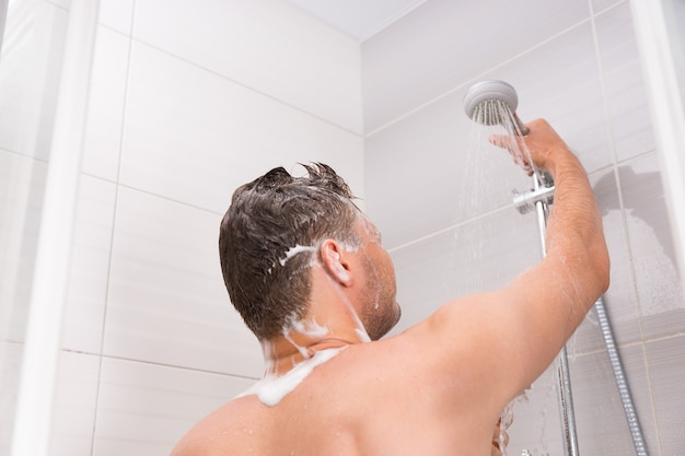Male holding shower head with flowing water in shower cabin with transparent glass doors in the modern tiled bathroom