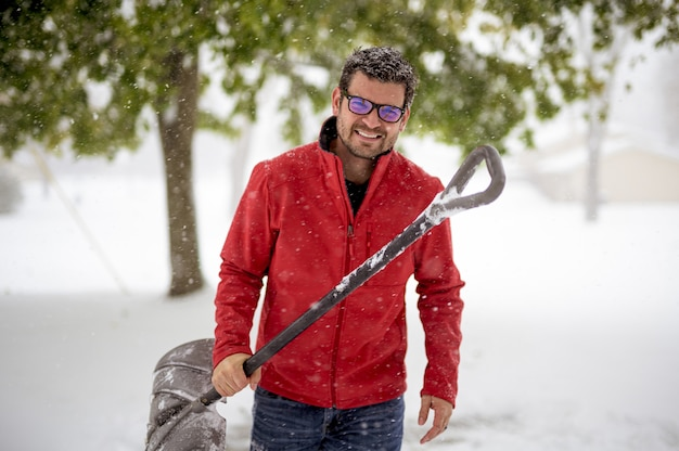 Male holding a snow shovel and wearing a red jacket while smiling