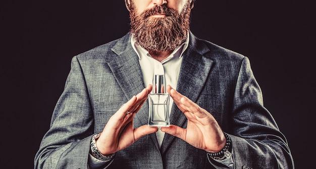 香水のボトルを保持している男性。男の香水、香り。香水またはケルンのボトルと香水、化粧品、香りのケルンのボトル、ケルンを保持している男性。男性的な香水、スーツを着たひげを生やした男