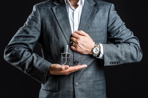 ボトルの香水を保持している男性。腕時計を手に
