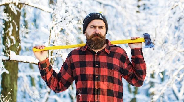 Мужчина держит топор на плече. брутальный бородатый мужчина. красивый мужчина, битник в заснеженном лесу.
