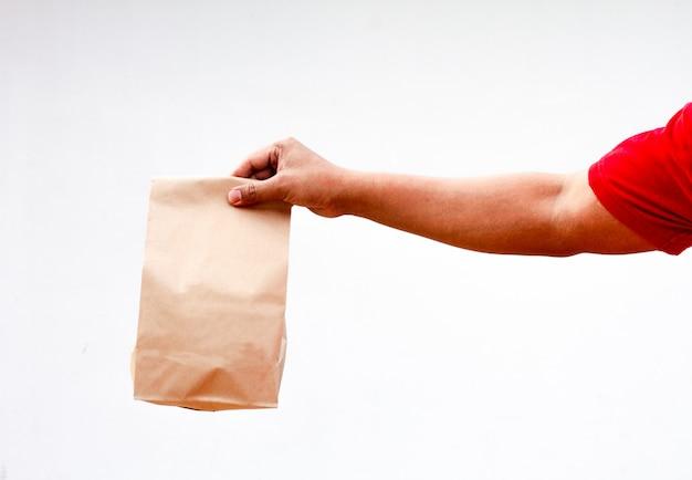 男性は、白い背景で隔離の持ち帰り用の茶色の明確な空空クラフト紙袋を手に保持しています。包装テンプレートのモックアップ。配信サービスのコンセプト。コピースペース。広告エリア