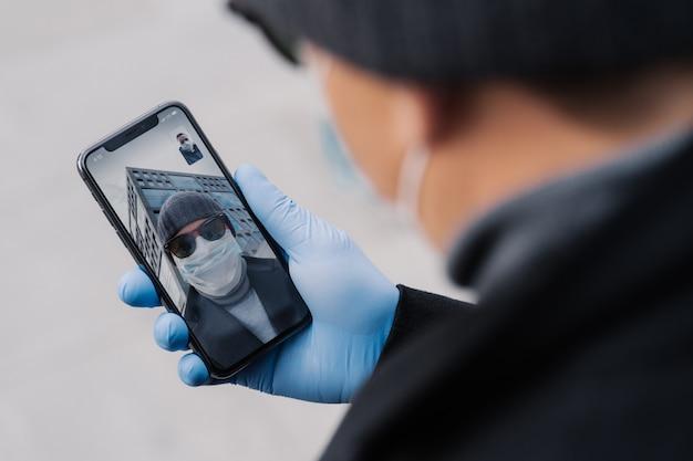 男性は医療用手袋をはめた電話を持ち、オンライン会議で友人と話し、友人に挨拶し、彼らの国でのコロナウイルスに関する最新ニュースについて話し合います。医学、医療、ビデオ相談