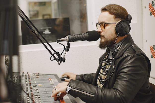 マイクで通信している男性のホスト。ラジオスタジオの男。