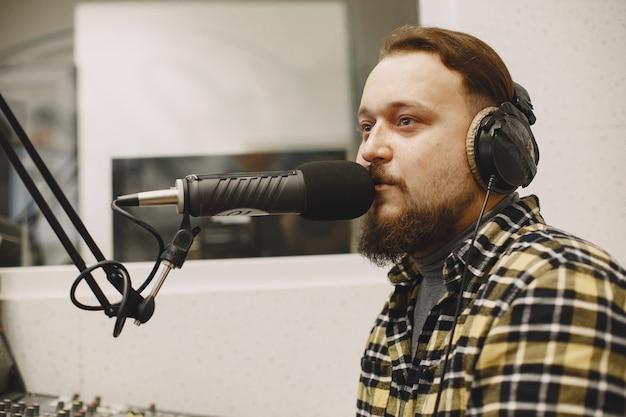 마이크에서 통신하는 남성 호스트. 라디오 스튜디오에서 남자.