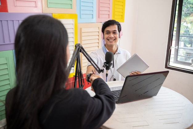 A male host shakes hands with a female guest during a podcast