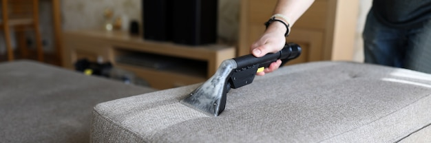Male housekeeper hand cleaning sofa with washing suction cleaner