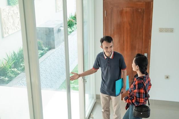 男性の住宅開発業者が手振りでガラスのドアのそばに立ち、女性に新しい家の裏庭を見てもらうように誘う