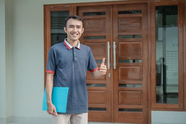 Застройщик мужского пола стоит с большим пальцем вверх и держит домашний сертификат против нового дома
