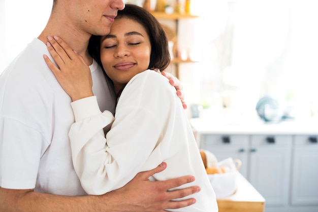 Male hugging ethnic smiling girlfriend with closed eyes