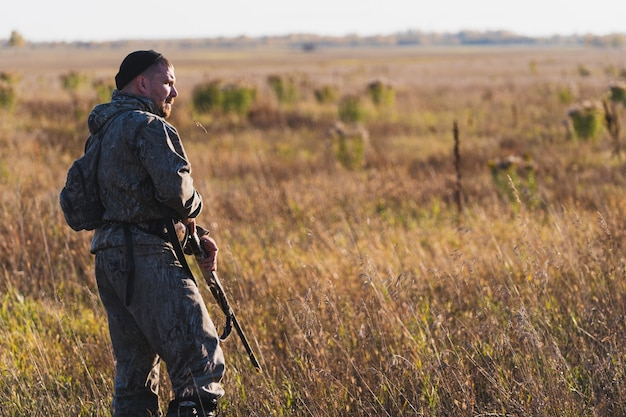 狩猟用ライフルで狩りをする準備ができている迷彩服の男性ハンター