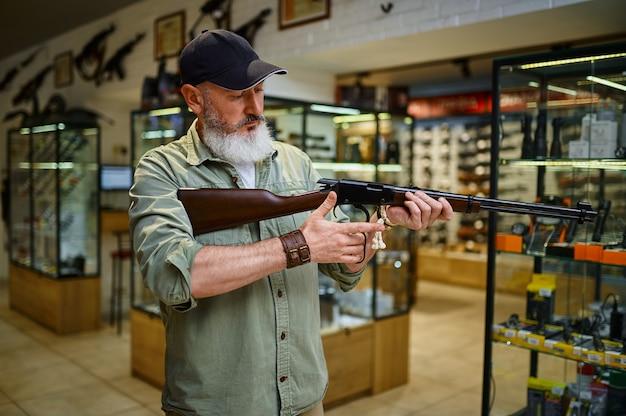 Мужчина-охотник перезаряжает винтовку в оружейном магазине. интерьер оружейного магазина, ассортимент патронов и боеприпасов, выбор огнестрельного оружия, хобби и образ жизни.