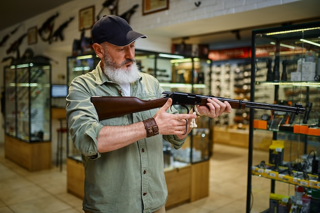 Мужчина-охотник перезаряжает винтовку в оружейном магазине