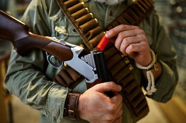 Bandolier와 남성 사냥꾼은 총기 저장소에서 소총을 로드합니다. 무기 상점 인테리어, 탄약 및 탄약 구색, 총기 선택, 사격 취미 및 라이프 스타일