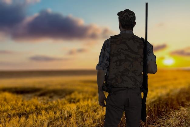 自然な背景にライフルを持つ男性ハンター
