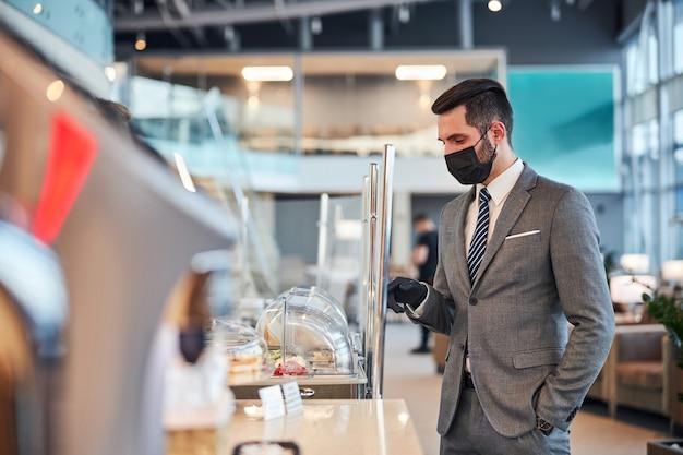 ビストロで食べ物を選ぶ医療マスクの男性