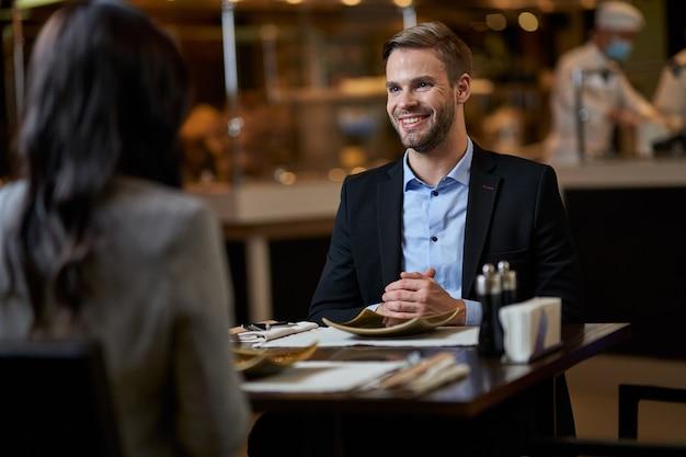 비즈니스 정장과 셔츠를 입은 남성은 손바닥을 테이블에 함께 접고 그의 여성 동반자를 응시합니다.