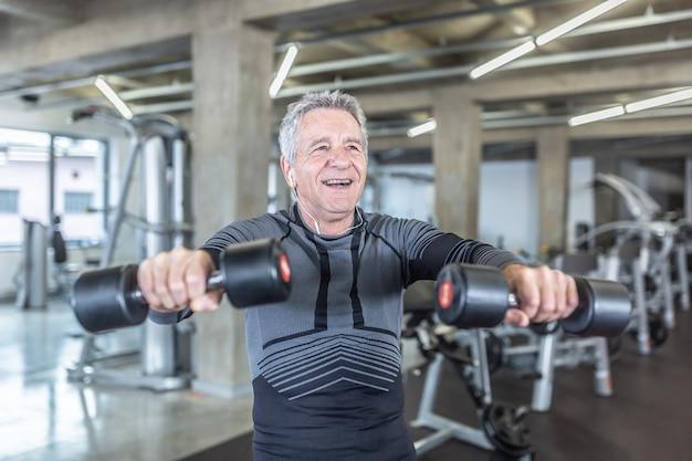 60대 남성이 피트니스 센터에서 덤벨 운동을 즐깁니다.