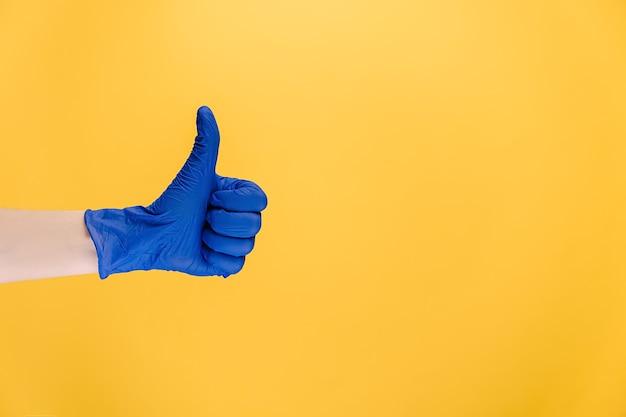 Мужчина в медицинских перчатках делает жест вверх пальцем