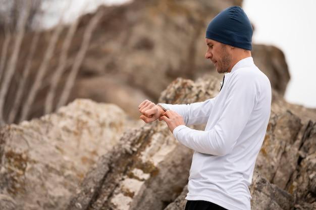 Мужчина в природе смотрит на часы возле скал