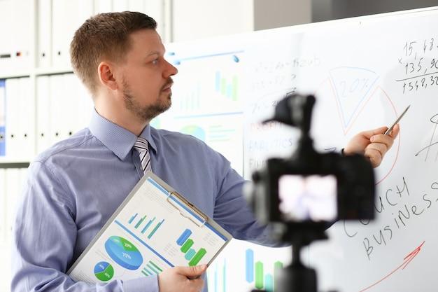 Мужчина в костюме и галстуке показывает диаграмму статистики