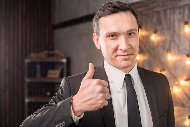 Мужчина в костюме показывает большой палец вверх
